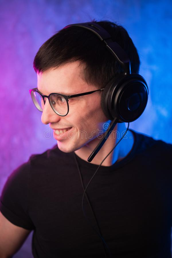 Gamer or streamer in earphones with microphone over colorful pink and blue neon lit wall stock photo