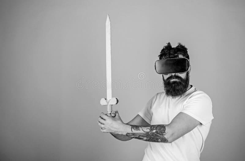 Gamerconcept Mens met baard in VR-glazen, lichtblauwe achtergrond Hipster op ernstig gezicht geniet spel van spel in virtueel stock afbeelding
