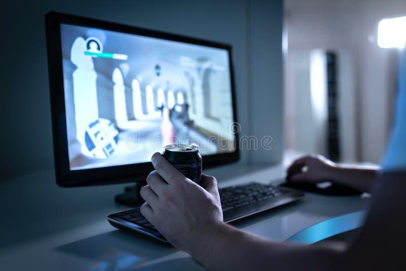 Gamerkerl, der Videospiel spielt und Soda- oder Energiegetränk von der Dose trinkt Fps-Videospiel im Computermonitor lizenzfreies stockfoto