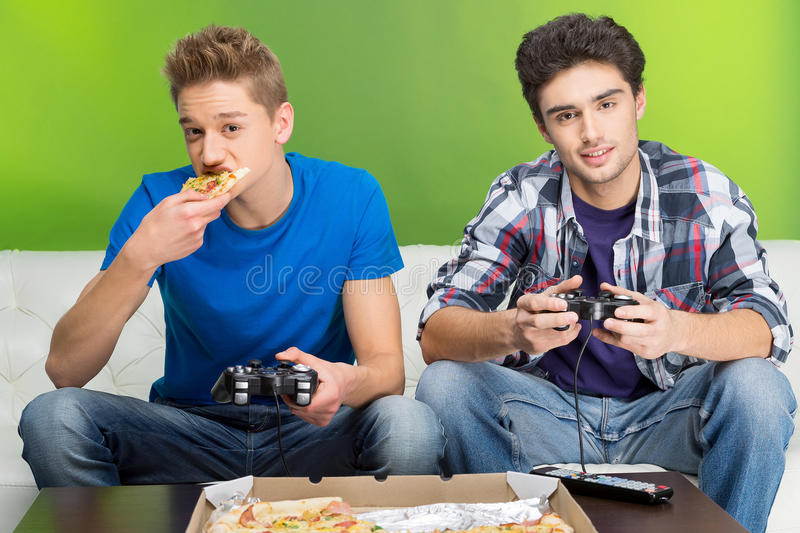 Gamers with joystick. Two young gamers playing video games while sitting on the couch royalty free stock image