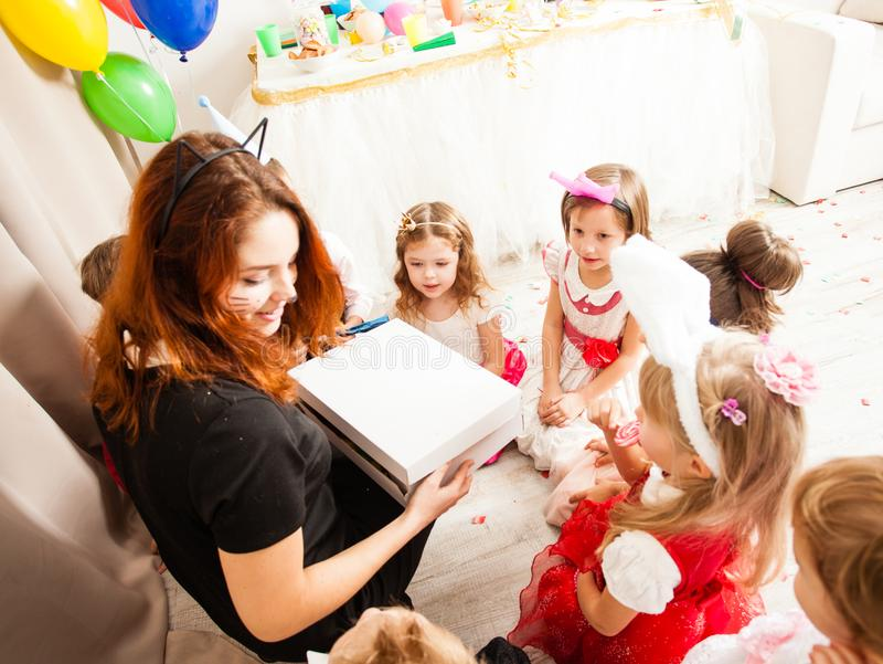 The games with animator. Cute kids playing with animator on the birthday party. Cat women entertains the guests stock photo
