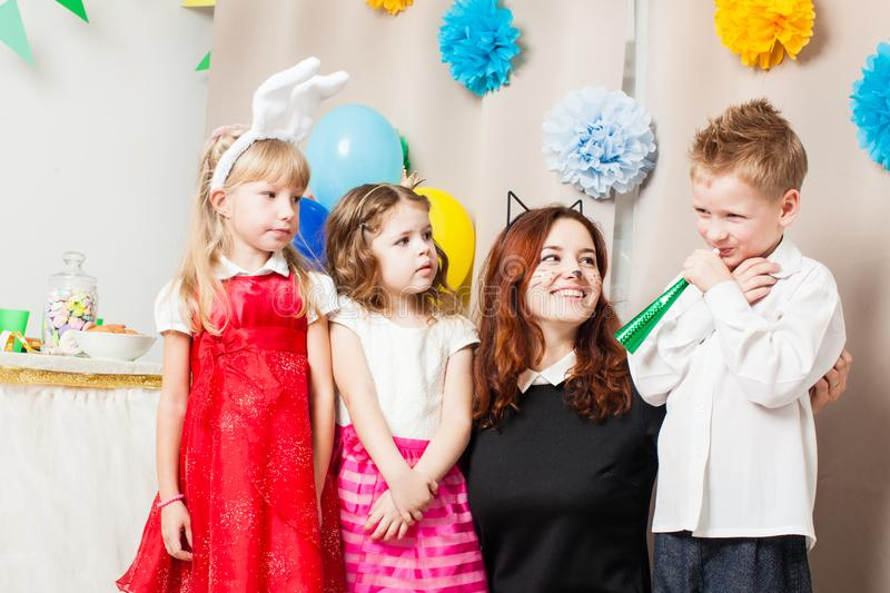 The games with animator. Cute kids playing with animator on the birthday party. Cat women entertains the guests royalty free stock photo