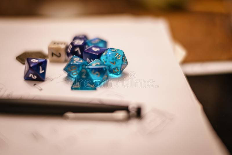 Gaming dice for role playing. Dungeon and dragons or pathfinder or other role playing games use polyhedral dice with pen pencil and paper royalty free stock images