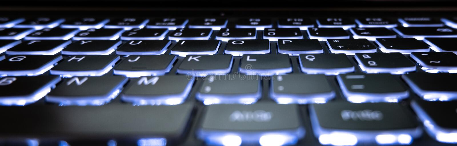 Gaming laptop computer keyboard with backlit keys. Low angle. Shallow depth of field royalty free stock images