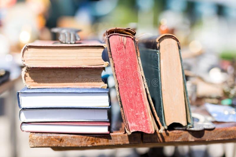 Gamla åldriga böcker på loppmarknaden Retro litteratur för tappning på trätabellen utomhus Bakgrund för gataswapmöte royaltyfri bild