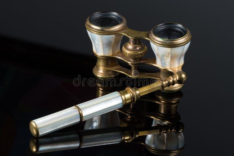 Gamla antika operaexponeringsglas som ligger på svart reflekterande yttersida royaltyfri foto