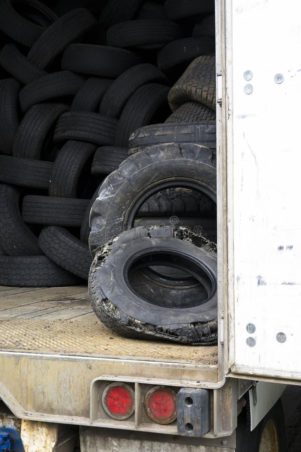 Gamla använda gummihjul lagras inom en gammal halv släp med en ope arkivbild