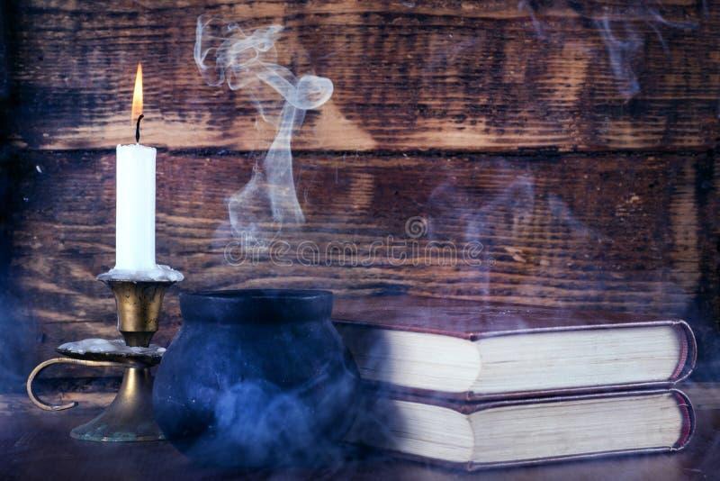 Gamla böcker av magi och häxan lägger in med rök och stearinljuset royaltyfri bild