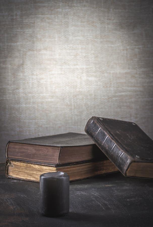 Gamla böcker för bön med en förstoringsapparat och en svart stearinljus royaltyfria bilder