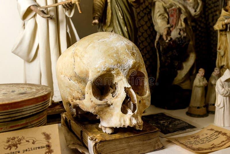 Gamla böcker för skalle på tabellen och medeltiden för tryck arkivfoto