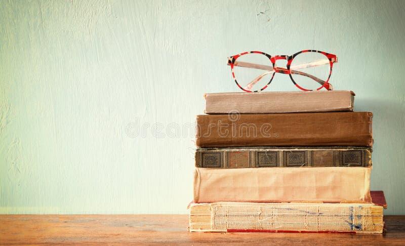 Gamla böcker med tappningexponeringsglas på en trätabell retro filtrerad bild royaltyfria bilder