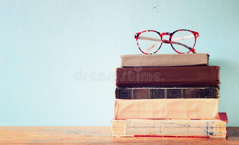 Gamla böcker med tappningexponeringsglas på en trätabell retro filtrerad bild royaltyfri fotografi