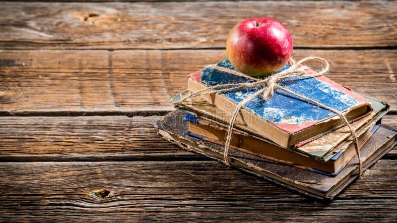 Gamla böcker och äpple på skolaskrivbordet royaltyfria foton