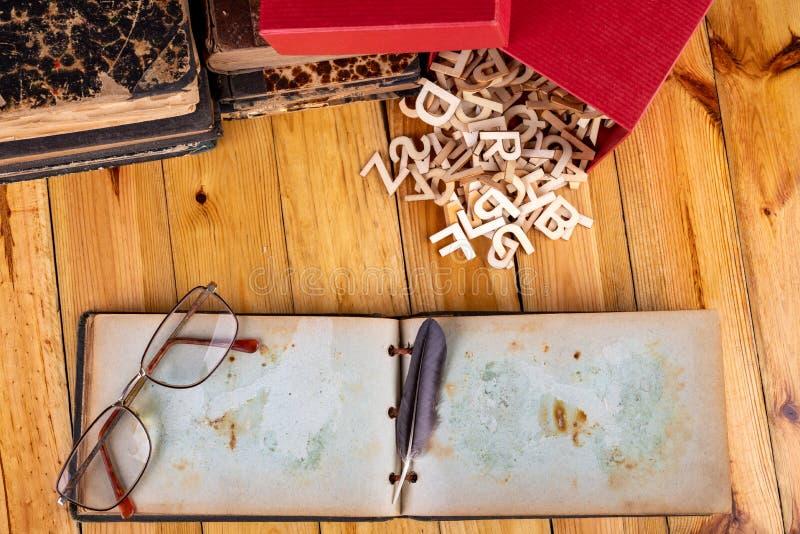 Gamla böcker och en anteckningsbok på en trätabell Bokstäver som klipps från trä som ordnas på en gammal anteckningsbok arkivfoto