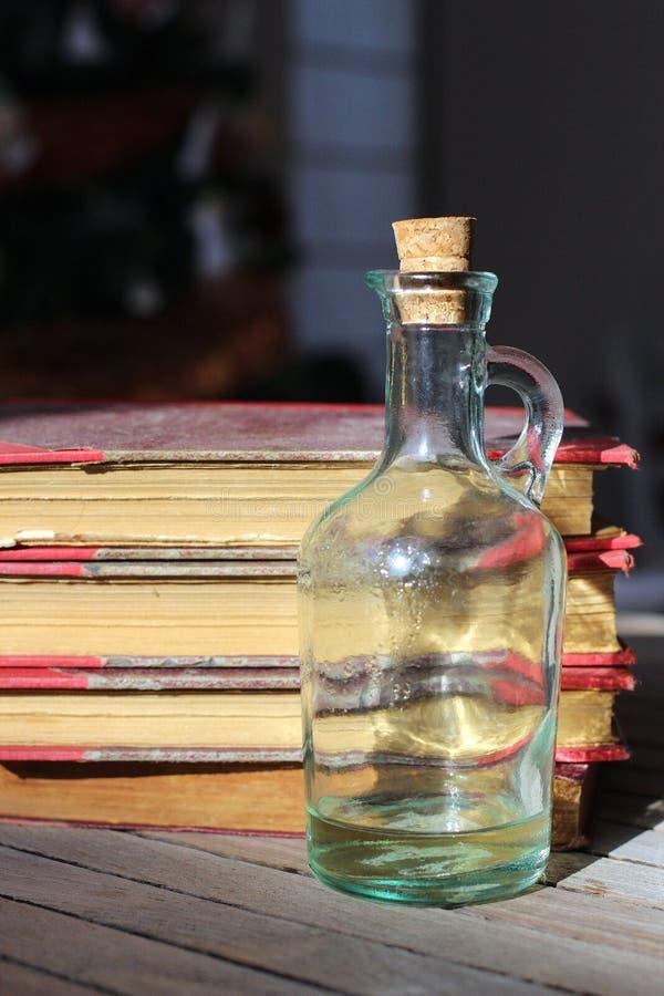 Gamla böcker och en flaska royaltyfri bild