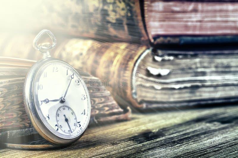 Gamla böcker och gamla klockor royaltyfri bild