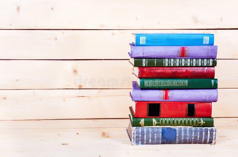 Gamla böcker på en trähylla fonder för utbildning arkivbild