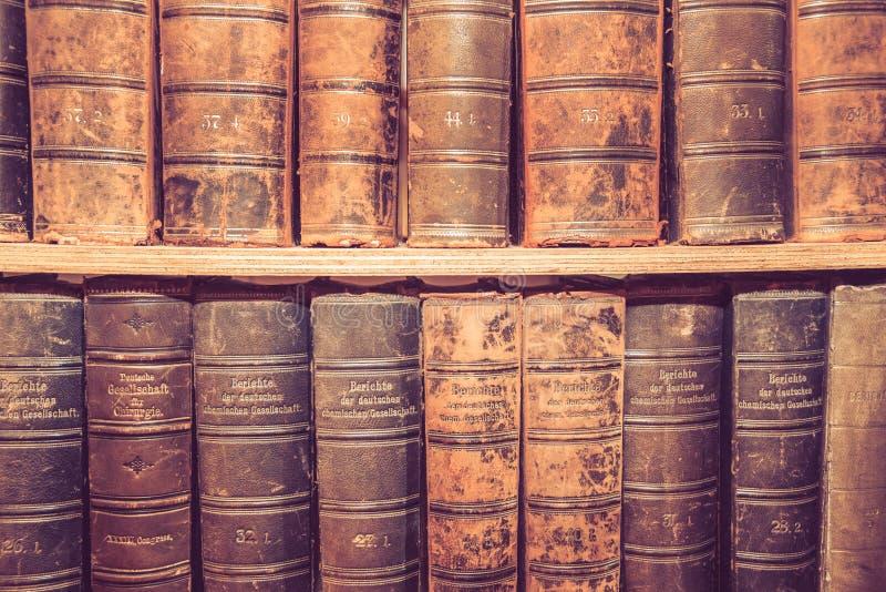 Gamla böcker på trähylla royaltyfria foton