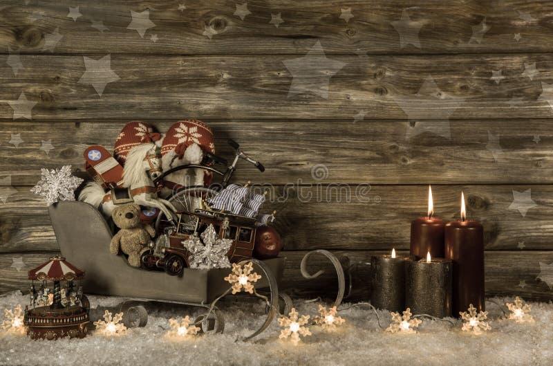 Gamla barnleksaker och fyra brinnande adventstearinljus på trävint fotografering för bildbyråer