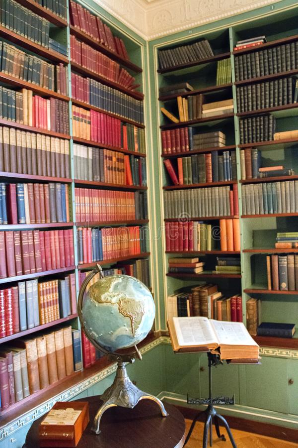 Gamla bibliotek med många böcker på hyllan i ett hem arkivbilder