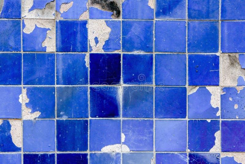 Gamla blått belägger med tegel väggen med sprickor och faller av royaltyfri foto