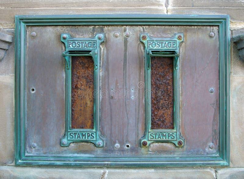 Gamla brittiska post- postaskar med rostade bokstavsspringor och utsmyckade gröna kopparramar med ordportostämplarna omgav arkivfoton
