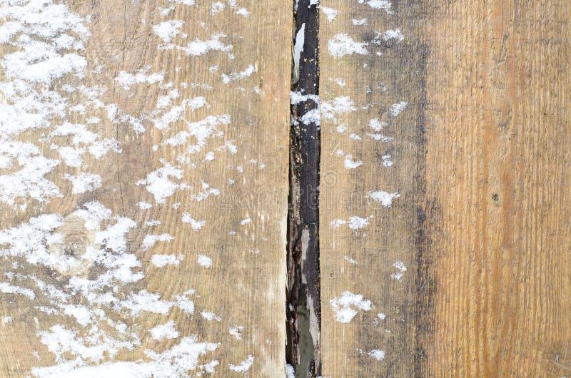 Gamla bruna bräden under snön royaltyfria bilder