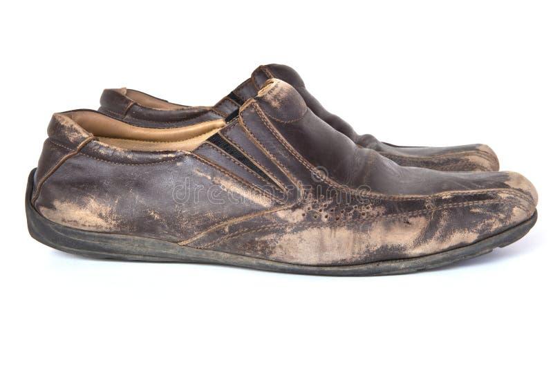 Gamla bruna läderskor på vit bakgrund royaltyfria bilder