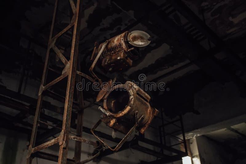 Gamla brutna rostiga etappstrålkastare i övergiven teater fotografering för bildbyråer