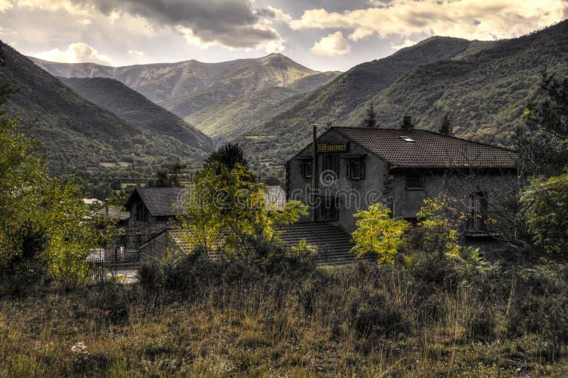 Gamla byggnader för en stad till och med grönska som framme lokaliseras av den djupa dalen royaltyfri bild