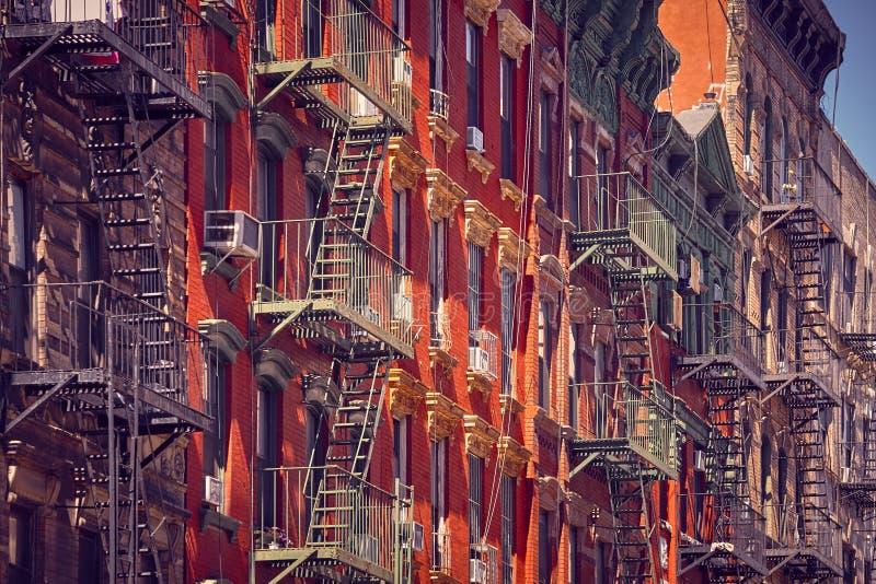 Gamla byggnader med brandflykter på solnedgången, NYC arkivbild