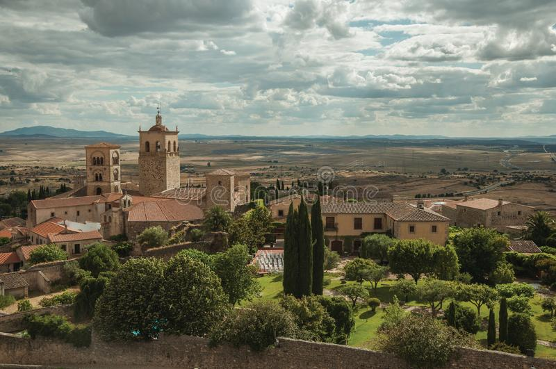 Gamla byggnader med kyrkliga kyrktorn och trädgårdar i ett lantligt landskap som ses från slotten av Trujillo arkivbild