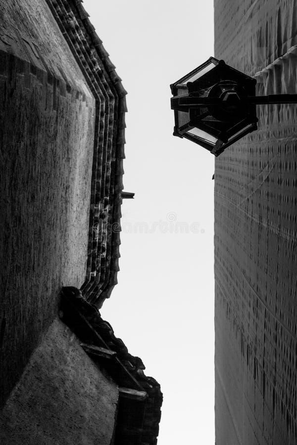 Gamla byggnader med perspektiv till den svartvita himlen arkivfoton