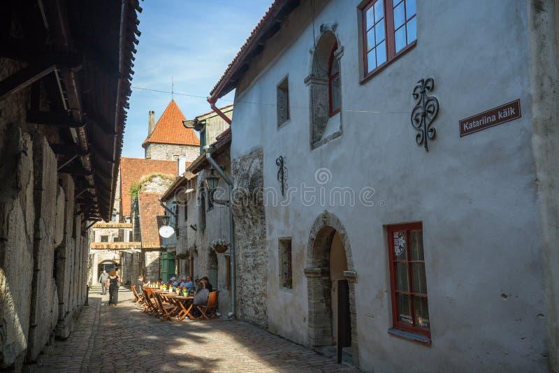 Gamla byggnader och turister på den gamla staden i Tallinn royaltyfri fotografi