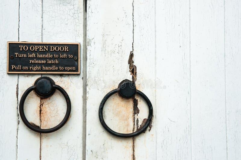 Gamla dörrhandtag med anvisningar royaltyfri bild