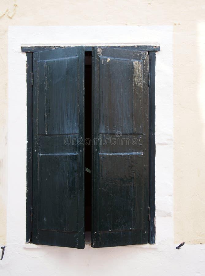 Gamla delvis öppna svarta målade träfönsterslutare i en vit ram på väggen av ett gammalt spanskt hus arkivfoton