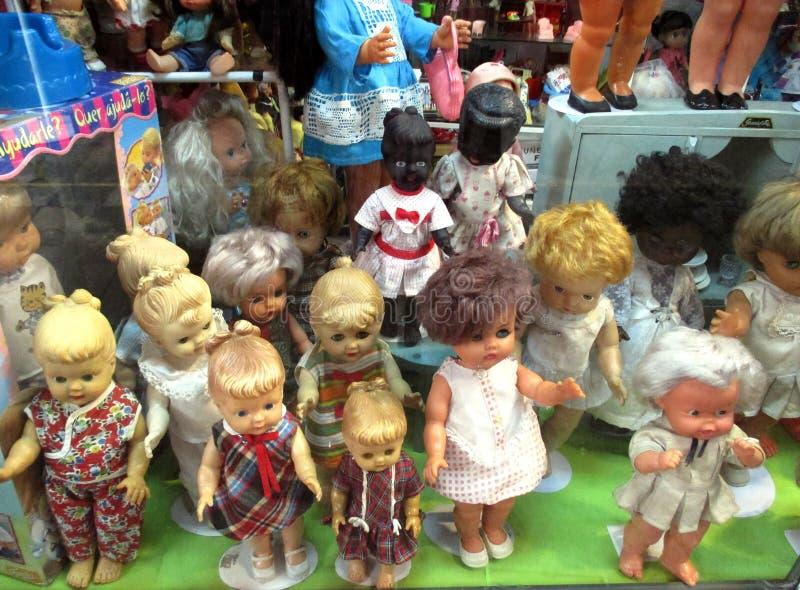 Gamla dockor i fönstret av ett leksaklager royaltyfri fotografi