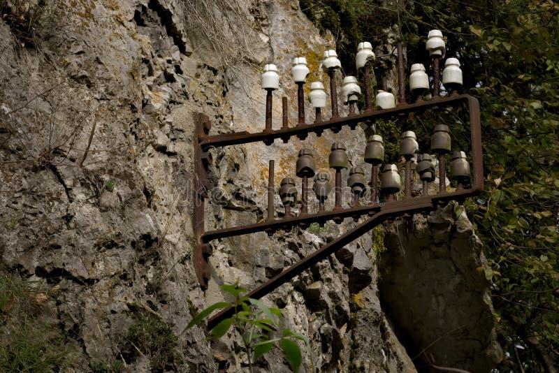 Gamla elektriska isolatorer på en vaggavägg arkivbilder