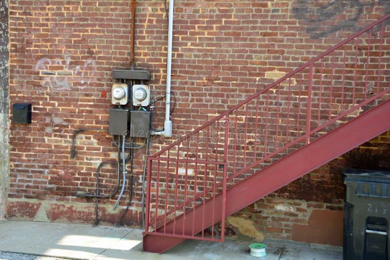 Gamla elektriska meter utvändig byggnad arkivbild