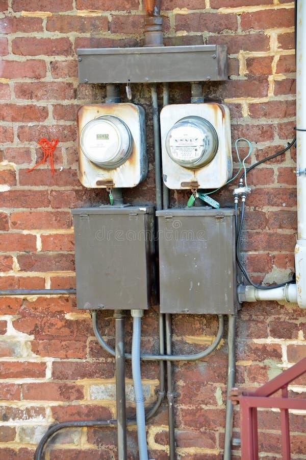 Gamla elektriska meter utvändig byggnad royaltyfria foton