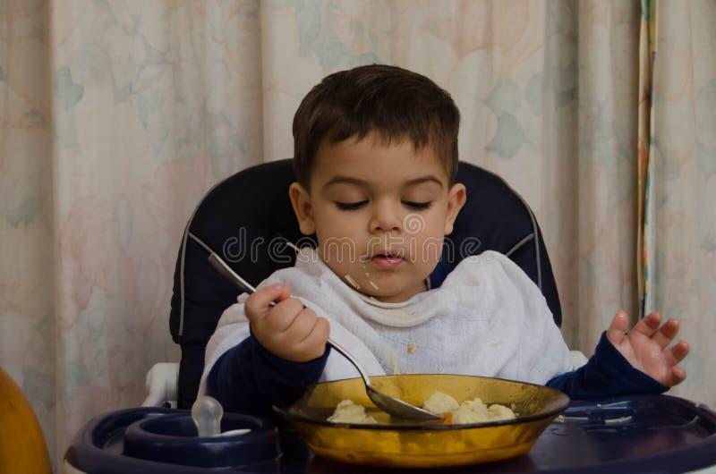 Gamla en och halva år behandla som ett barn pojken som äter soppa med skeden royaltyfri fotografi
