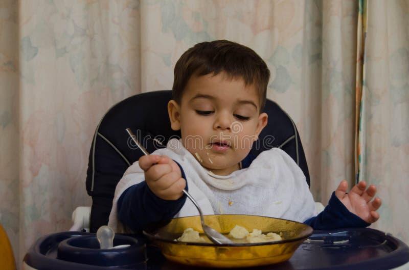 Gamla en och halva år behandla som ett barn pojken som äter soppa med skeden arkivbild