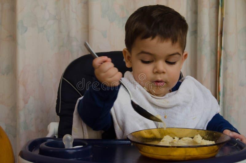 Gamla en och halva år behandla som ett barn pojken som äter soppa med skeden arkivfoton