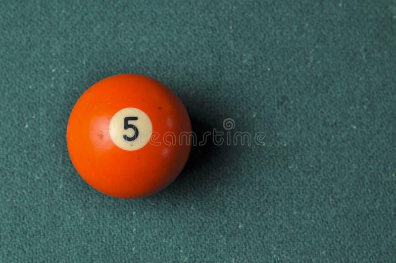 Gamla färg för nummer 5 för billiardboll orange på den gröna billiardtabellen, kopieringsutrymme arkivfoto