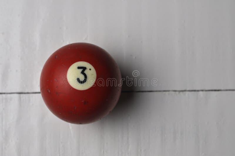 Gamla färg för nummer 3 för billiardboll röd på vit trätabellbakgrund, kopieringsutrymme fotografering för bildbyråer