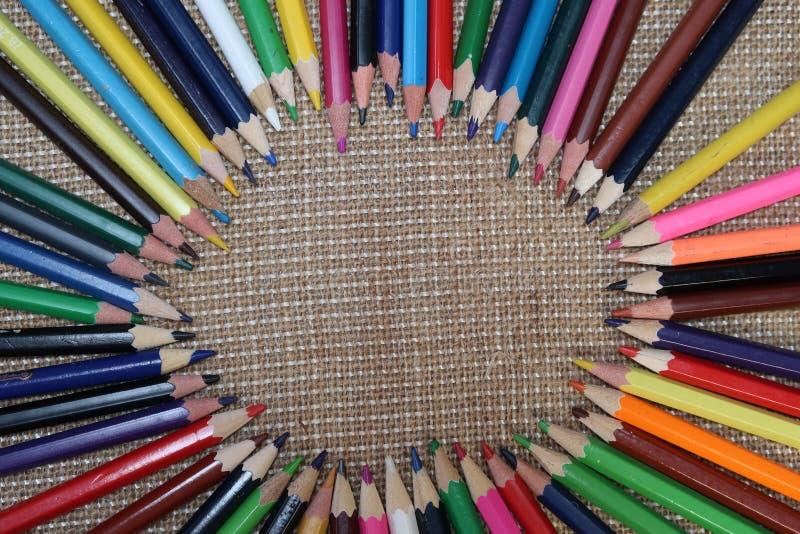 Gamla färgblyertspennor på säckvävbakgrund arkivfoton