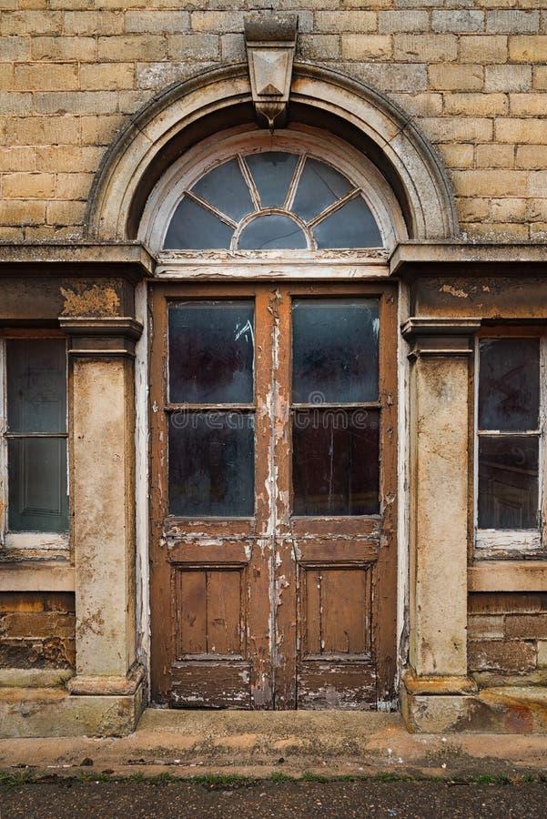 Gamla förfalla trädubbla dörrar arkivbild