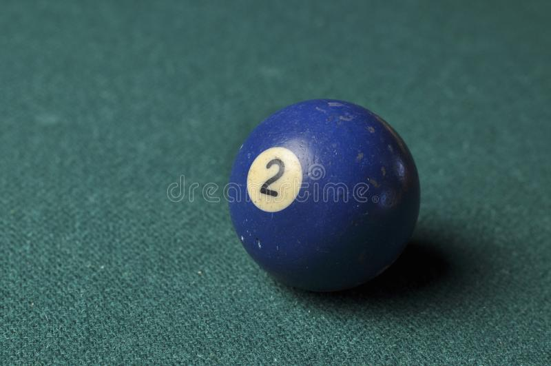 Gamla f?rg f?r nummer 2 f?r billiardboll bl? p? den gr?na billiardtabellen, kopieringsutrymme fotografering för bildbyråer
