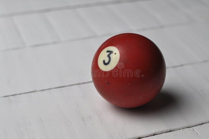 Gamla f?rg f?r nummer 3 f?r billiardboll r?d p? vit tr?tabellbakgrund, kopieringsutrymme fotografering för bildbyråer