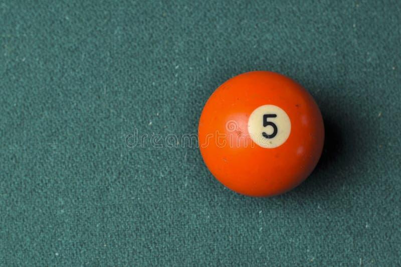 Gamla f?rg f?r nummer 5 f?r billiardboll orange p? den gr?na billiardtabellen, kopieringsutrymme arkivfoto
